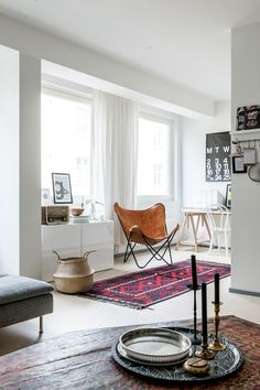 Tour of a bright white helsinki home // love the bright pink rug + cognac leather butterfly chair