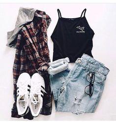 Camisa a cuadros roja, musculosa negra, zapatillas adidas all Star y jeans azules rotos y sueltos