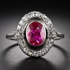rich, luscious red, oval Burma ruby, weighing 1.15 carat but presenting significantly larger due to its spready cut, floats inside a sparkli...