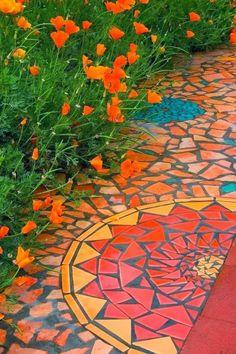 Mosaic garden path. Love how the orange matches the orange flowers in the garden.