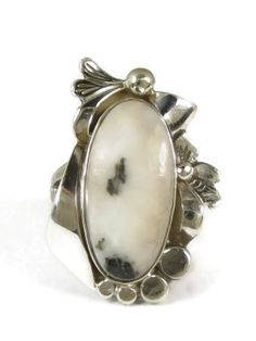 """Silver White Buffalo Ring Size 6 by Les Baker Jewelry. This is a beautiful silver ring adorned with a White Buffalo gem from Nevada made by Ted Secatero and designed by Les Baker Jewelry. The gem is in a deep, smooth silver bezel encircled by silver leaves and beads, 13/16"""" by 3/8"""". The ring is 1 1/4"""" by 13/16"""" at the widest section. Elegant design. Signed by the artist. #southwestrings www.southwestsilvergallery.com"""