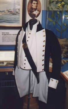 Replica of a British Royal Navy Lieutenant's Uniform, circa 1800-1811.  This image shows a Lieutenant's full dress uniform including a detail of the button twist on the lapels and collar along with the belt plate and an undress fore-and-aft bicorn (chapeau bras).  While the 1795 dress regulations established this uniform, its cut matches that of the post-1800 period like at the Battle of Trafalgar.