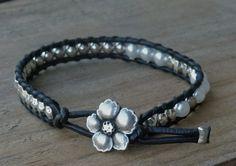 Pulsera en cuero negro,hecha a mano.Combinación de perla blanca y cuentas en plata.Botón pequeña flor de Hibiscus.
