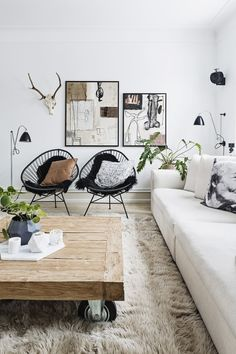 Abstract art even has its place in a warm and cosy interior. The organic shapes and earth colours of these works make them a right fit for a room which is given warmth by a big rug, plants and a rough wooden table.