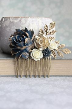 This is a beautiful flower hair comb in dark navy blue, ivory cream and gold! The large navy rose has gorgeous gold edged petals and is set on one side of this floral collage. Balancing out the other side of this floral collage is a bouquet of resin flowers in ivory cream, gold and dark navy blue! Layers of leafy branches in antique brass add lovely details to this floral collage hair comb! This would make a gorgeous bridal hair accessory or would be a fun accessory to make any day feel…