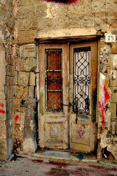 Undying Purpose - Although the crumbling house has been abandoned, the door refuses to fall and give up its initial purpose of guarding it. There is so much soul in this image. Photo taken in the quarter of Niochori, Rhodes www.anna-wacker.photography