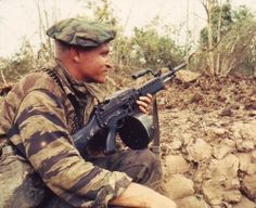 A Navy SEAL in Vietnam keeps his Stoner 63A light machine gun at the ready while the rest of his squad prepares demolition charges on a Vietcong bunker. The weapon is fitted with a 150-round drum belt container and is fed from the left-hand side. The retracting handle is locked forward and the ejection port closed with a dust cover to minimize dirt entry.