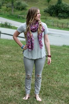 A fun look featuring grey ripped jeans, a grey shirt and a pop of color with a floral scarf