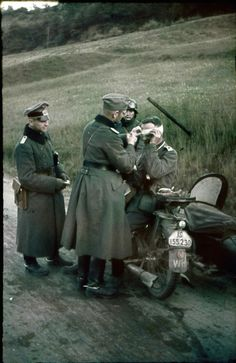Wehrmacht Soldiers of the 71st Infantry Division provide medical attention using a motorcycle steady a wounded soldier