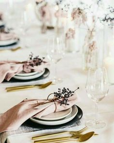 Simple table decor with pink napkins and dried black berries, glass ware and brass cutlery.