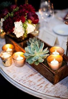 Succulent centerpiece with candles and just no on red and white flowers. other colors.