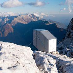 This tiny aluminium-clad cabin designed by Slovenian studio OFIS Arhitekti cantilevers over the edge of a mountain on the Slovenian-Italian border