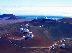 An aerial photograph of the Mauna Kea observatories at the summit of Mauna Kea in Hawaii. The ocean is visible in the far background, while the layout of the facility in the foreground shows the location of several large telescopes.