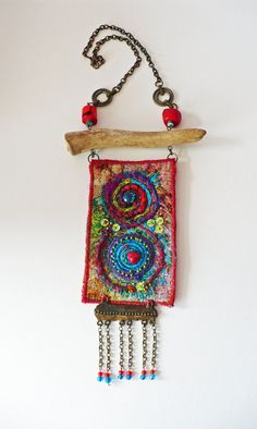 This necklace has a chain of metallic, bronze color and has a carbijnsluiting. length 45cm. The pendant is hanging on a stick of wood, length 12cm. The pendant is of tapestry fabric which is embroidered with tiny glass beads, silk thread and sequins. height 12cm, width 7cm. Below hangs a vintage metal ornament. The deep red beads or coral. This jewelry is made with care and love and is unique