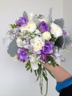 Bridal wedding bouquet of roses, ranunculus, babies breath, freesias, tetra nuts and dusty miller in whites, greys, silvers, and mauve/light purples.