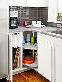 A lazy Susan is a great solution for a corner cabinet. Remove the corner door to make it easy to see what's in the cabinet. A narrow cabinet is a convenient spot for cooking sheets and cutting boards. Hanging bars, above, pull out for dish towels.