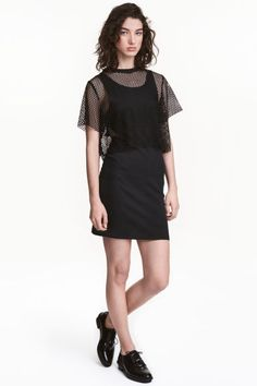 Dress with a mesh top: Short, fitted, sleeveless dress in jersey with cut-out sections at the sides. Sewn-on mesh top with short sleeves and raw edges.