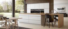 cuisine blanche moderne aménagée avec un grand îlot central, équipé d'un bar petit déjeuner en bois massif