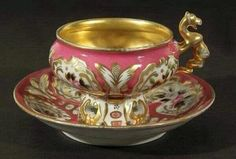 ANTIQUE RUSSIAN KORNILOV PROCELAIN CUP SAUCER PARDALOKAMPOS HANDLE, KOMILOV BROTHERS FACTURY, CIRCA 1835-1840.CUP OF BULBOUS FORM ON A PERFORATED FOOT, EXTERIOR OF CUP SND CASVETTO OF SAUCER DECORATED WITH GILT CARTOUCHES ON GROUND SURROUNDING DELICATE HAND PAINTED IMAGES OF FLOWERS, INTERIOR OF CUP DECORATED WITH GILDED SCROLLWORK.
