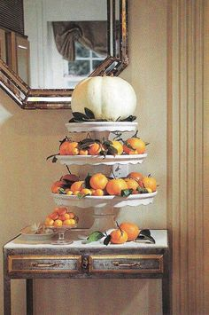 A seasonal centerpiece pumpkin, fruits, and pastry stands of graduated sizes.  Use mandarins, oranges or persimmons for the edible color.