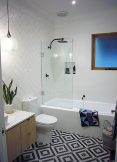Stunning bathroom featuring Phoenix Tapware matte black taps and wonderful pattern tiles and towels