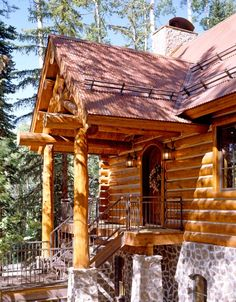The entry of this home features structural log scissor trusses, log purlins and log support posts.  The exterior is a combination of white cedar log finishes with chinking and natural stone.