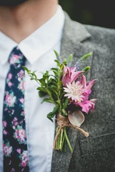 This boho chic wedding has a rustic boutonniere and a matching tie. The grey suit looks so handsome here. These modern grooms love their florals.