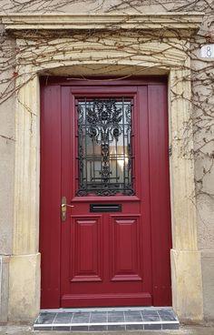 Porte en bois rouge avec grille en fer forgé