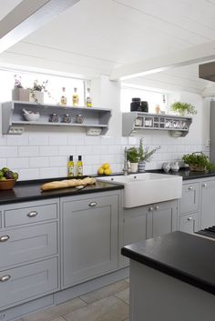 Swedish hand painted kitchen in grey with white tiles, glass jars and Belfast sink