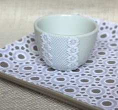 Add texture to bowls and vases by Mod Podging lace to the surface and then painting over