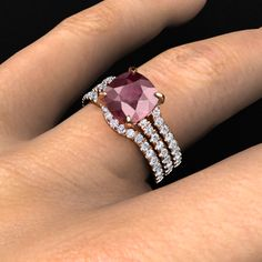 Cecilia ring in rose gold with rhodolite garnet center stone and diamond accents. Matching band on each side in rose gold with diamonds.