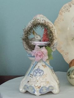 "This adorable decoration is the perfect Easter Gift! It features a vintage plastic bunny with hand dyed, glittered bottle brush trees and Easter Egg.  Finished with plenty of sparkle, tinsel and vintage charm.      A little treasure for your favorite Easter bunny!    This handmade, one of a kind item measures approximately 8"" tall and 5"" wide. 