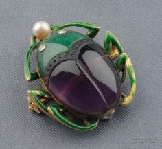 A gold, aventurine, and amethyst pendant by Marcus & Co, c.1910, in the form of a scarab beetle; the symbolic reference is to ancient Egypt, and to the god Khepri, a form of the sun god who pushes the solar disc across the sky.