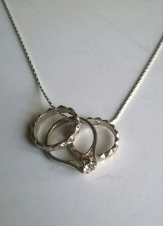 Beautiful little detailed vintage rings on a chain. All sterling silver, one set with a tiny diamond look stone. 16 inch snake chain. Really pretty.