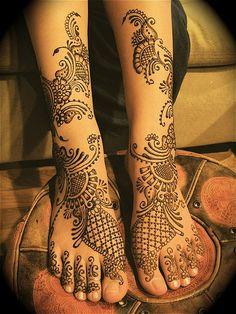 mehndi henna design on legs and feet. Body art.