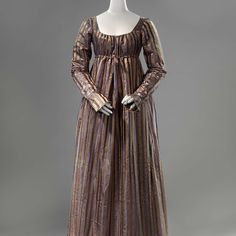 Ankle-length gown with a ruffled edge, c. 1815 - c. 1820 silk,  In the early years of the 19th century, mainly sheer, pale-coloured fabrics were preferred. From 1815 darker colours also became fashionable. This silk may be slight in quality, but its pattern is quite intricate. The brown bands are of a satin weave and the blue bands have vertical stripes woven into them. http://hdl.handle.net/10934/RM0001.COLLECT.323480