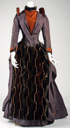 Ensemble: ca. 1888-1890, American (probably), silk.   Unusual color combo...I love it! The springy shoulder wings and the Tron-esque velvet are the icing on the cake.