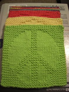 A Knitting Mountain: Peace Washcloth Pattern.  This site also has heart and smiley face with the patterns