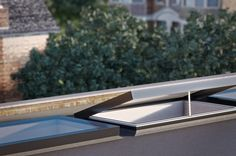 External view of EOS Opening and Fixed roof light showing fully open sky light and actuator chain on flat roof extension.
