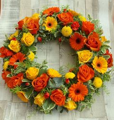 Bright wreath with vivid yellow and orange gerbera, yellow and orange roses and seasonal foliage.