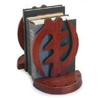 """Ghana's famed gye nyame symbol emerges in cedar wood, its rotating form meaning """"I fear none except God."""" Known as an adinkra symbol, this image is revered throughout the country. George Obeng carves the traditional motif to grace a pair of bookends."""