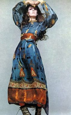 Anjelica Huston vintage fashion style color photo print ad 70s boho dress long sheer graphic print blue rust red sheer belt long sleeves boots movie star