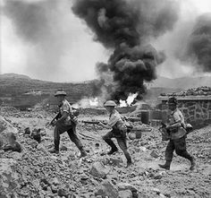 Lance Sergeant A Haywood, Private C Norman and Private H Maw of 1st Battalion, The British Duke of Wellington's Regiment advancing past a burning fuel store on Pantelleria, 17 Jun 1943. (Imperial War Museum)