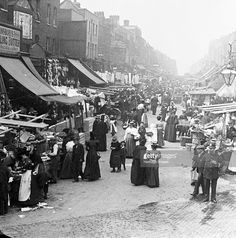 Chapel Market, Islington, London. The street is lined with market stalls and shops, and is bustling with shoppers. A policeman keeps an eye on things in the bottom right corner.