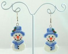 The item up for sale is a pair of beaded earrings. The design features a cheery snowman dressed in blue with a touch of holly on his hat. The main