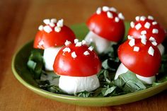Mozzarella Balls topped with half cherry tomatoes on a plate of fresh basil ~ Caprise Salad Mushrooms!  Too cute.