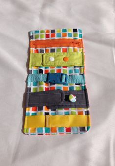 Busy blanket - a buckle, snap, zip, Velcro, and button toy - fine motor skills practice. $25.00, via Etsy.