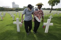 American Robert Dryfoos, left, from Conn., with Khalil Diallo walks around layers of tombs after attending Memorial Day rites at the American Cemetery in suburban Taguig, south of Manila, Philippines