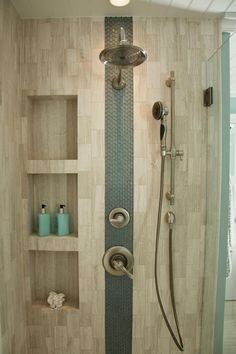 An accent stripe of glass tiles adds interest to this neutral shower. Sleek niches provide storage for shower essentials, and dual shower heads create a luxurious atmosphere.