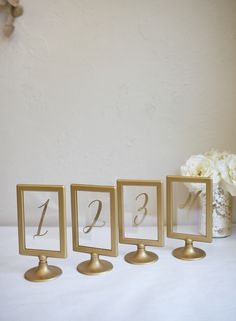 Gold framed IKEA table numbers with gold hand lettering.